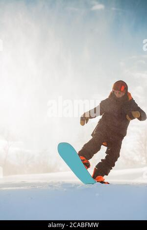 fearless snowboarder riding on a slope. active athlete is doing a trick. sportsman with a snowboard performing tricks - Stock Photo