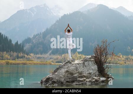 a zen man in white practices yoga in nature pose