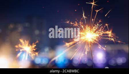 Happy New Year, Glittering burning sparkler against blurred city light background
