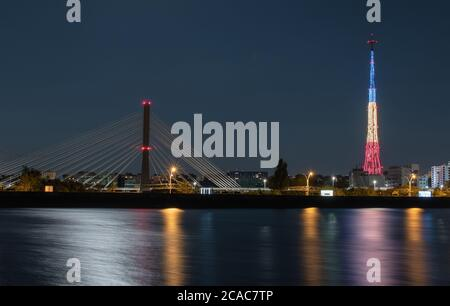 Light reflections in the water of the Mill Lake, coming from the tricolor illuminated tower, the street lighting and the road bridge
