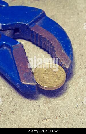 A british one pound coin in a wrench - Stock Photo