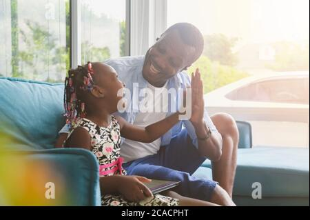 African father and daughter using looking tablet happy parents with kids relax at home in casual wear sitting on sofa in living room Stock Photo