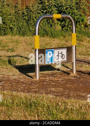 Support for bike with sign in English park land in summer