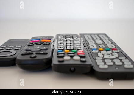 On a white background the remote controls, one for each device used. - Stock Photo