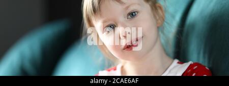 Little girl sitting at home sofa with piggy bank - Stock Photo
