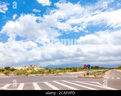 Beautiful view of wide open road with a paved highway stretching out as far as the eye can see with small green hills under a bright blue sky in the