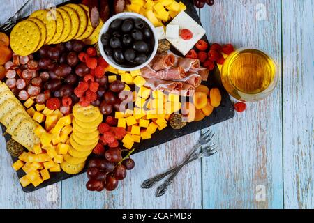Charcuterie board assortment, cheese, olives, fruits, prosciutto and wine on wooden table. - Stock Photo