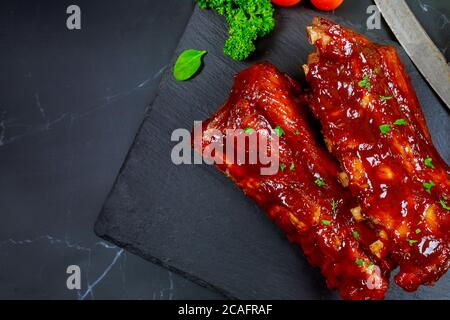 Pork ribs with barbecue sauce on black stone board. Top view with copy space - Stock Photo