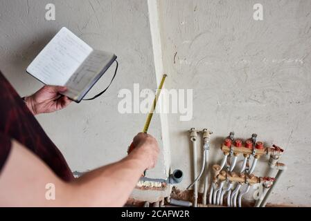 Close up of male hands holding notebook with building plan and using measuring tape. Man taking measurement while working on renovation of apartment. Concept of repair and refurbishment.