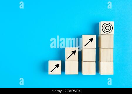 Business or economic growth concept with arrow icons on wooden cubes on blue background