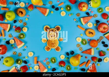 Kids healthy food concept. Fruits and vegetables with funny bear made from pancakes. - Stock Photo