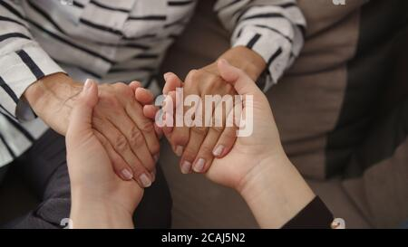 Close up, young woman and senior woman holding hands. Family bonding concept. High quality 4k footage