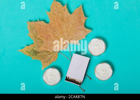 Three decorative candles in the shape of a flower. Next to them are a box of matches and dried maple leaves. On a mint background.