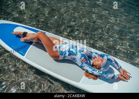 SUP Stand up paddle board. Young woman sailing on beautiful calm sea with crystal clear water. The concept of an summer holidays vacation travel - Stock Photo