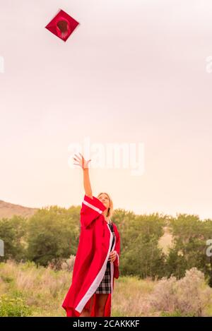 Beautiful young girl throwing red graduation cap in the air celebrating.