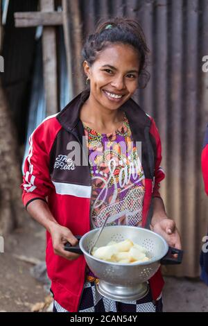 Haikesa / Indonesia - August 10, 2018: attractive young Timorese woman cooking with firewood in rural area near border between Timor and Indonesia - Stock Photo