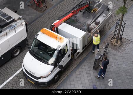 Garbage truck with worker in shopping street. He throws waste from the waste bins in a truck on behalf of a municipality Maastricht in the Netherlands - Stock Photo