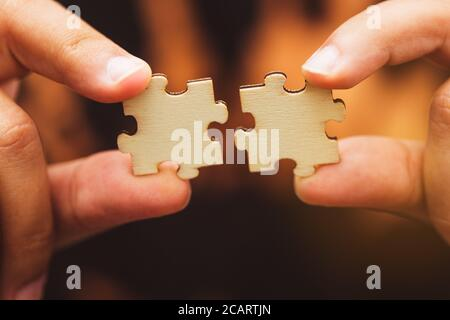 Man hand connecting jigsaw puzzle, Business solutions,Team work, success and strategy concept.