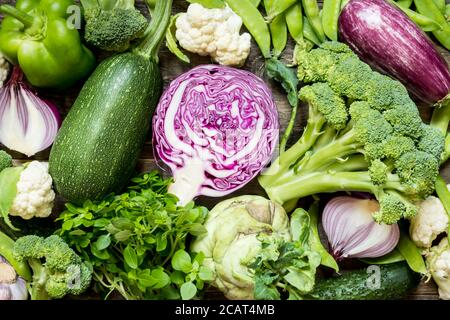 Top view set raw of green, red and purple vegetables spread on dark wooden background - Stock Photo