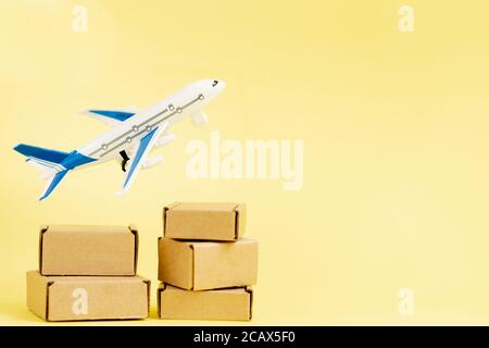 Airplane and stack of cardboard boxes. concept of air cargo and parcels, airmail. Fast delivery of goods and products. Cargo aircraft. Logistics