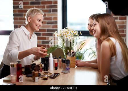 beautiful make-up artist and girls pupils discuss cosmetics on master class, professional visagist explain which of cosmetics for what is suitable for