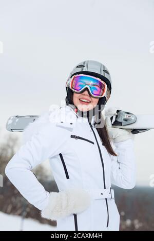 gorgeous woman in white stylish outfit spending a great time at ski resort, close up photo, - Stock Photo