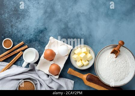 Ingredients for baking and kitchen utensils on blue background. Top view copy space for text or design