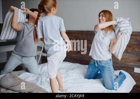 caucasian family consisted of mother father and kid girl having fun together playing with pillows at home on bed - Stock Photo