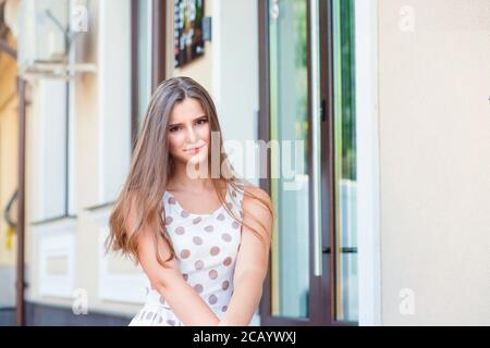 Outdoors portrait of a beautiful suspicious skeptical woman. Beautiful young girl in white dress with brown polka dots. Mixed race asian russian. Hori