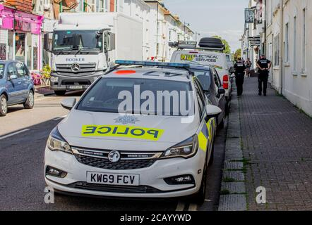 Two police officers walking away from their car in Norfolk Road, Littlehampton, West Sussex. UK - Stock Photo