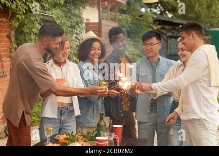 Multi-ethnic group of young people lighting sparklers while enjoying Summer party at outdoor terrace, copy space - Stock Photo