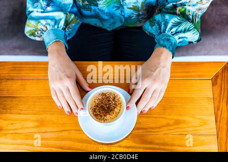 View from the top of two hands of a woman with red polish nail while drinking a cappuccino in a local coffee house in Lisbon