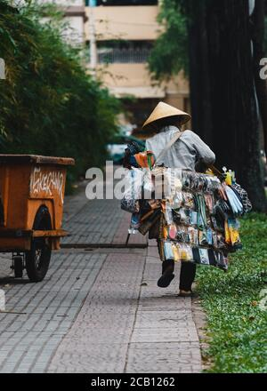 Ho Chi Minh city, Vietnam - 29 July 2020: Vietnamese women wearing Non la, street vendors, selling souvenirs and miscellaneous goods, walking on the s