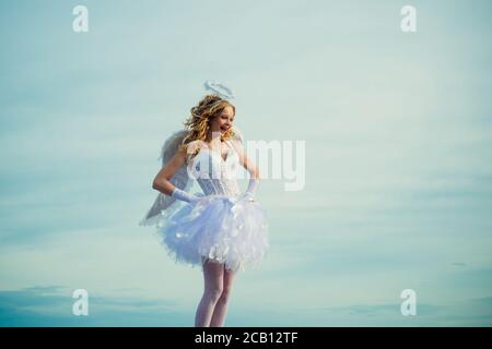 Charming curly little girl in white dress and wings - angel cupid girl. Enjoying magic moment. Pretty white little girl as the cupid with a bow and - Stock Photo