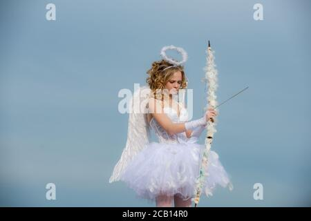 Cupid cute girl with a bow. A beautiful teen with blonde curly hair and a bow and arrow as cupid - Valentines Day. Bow and arrow. Festive Art Greeting - Stock Photo