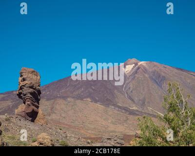 view on Roque Cinchado and colorful volcano pico del teide highest spanish mountain from famous rock formation Roques de Garcia with clear blue sky - Stock Photo