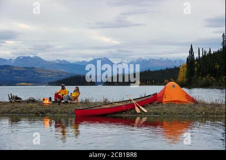 Couple around a campfire, canoeing, camping on the shore of a lake, Yukon Territory, Canada