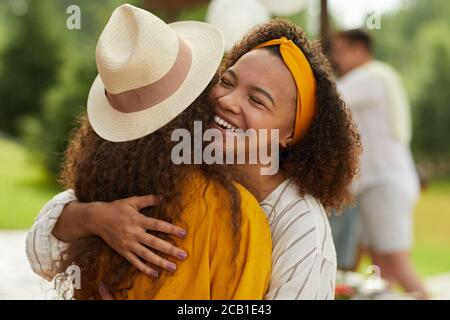Portrait of young African-American woman hugging friend and smiling cheerfully while enjoying outdoor party in Summer - Stock Photo