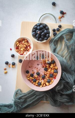 Pink yogurt with flakes and blueberries for summer breakfast, flat lay style - Stock Photo