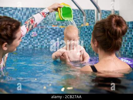 Image of swimming lesson for infants. Young mother holding her little baby, coach pouring out some water on baby's head. Concept of early development and care - Stock Photo