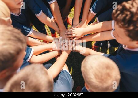 Happy kids sports team stacking hands at the field. Children team sports. Boys at sports camp stacking hands before a match. School age children in a