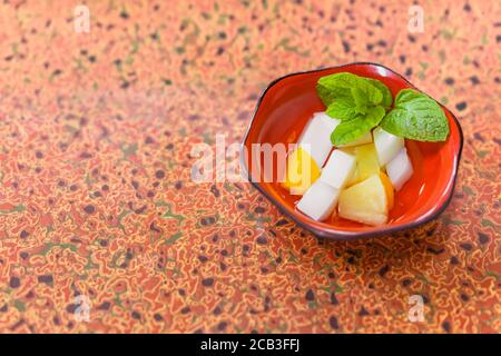 Japanese traditional dessert of Annin tofu or almond tofu made of apricot kernel milk, agar, and sugar with fruits pieces like pineapples and apricot