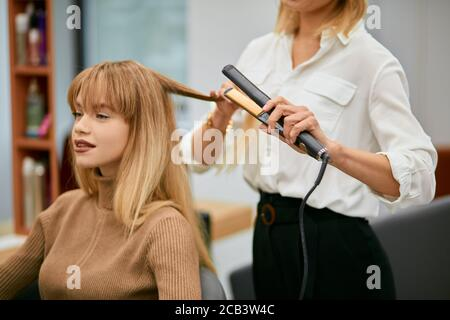 professional hair stylist making hairdo to young caucasian girl with long hair, careful hairdresser and young beautiful client in beauty saloon