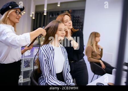 fashionable modern make-up artist doing makeup to young caucasian girl while hairdresser making hairdo in the background. Isolated in beauty saloon