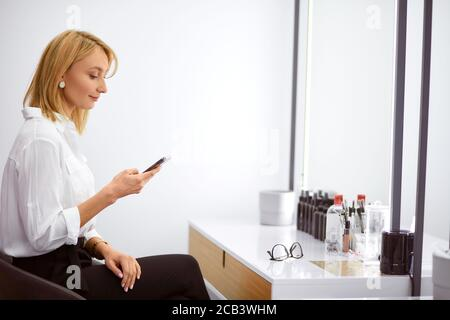 Young caucasian make-up artist resting at her work place, look at screen of smartphone , table with cosmetic pallete and brushes. Young blond woman in
