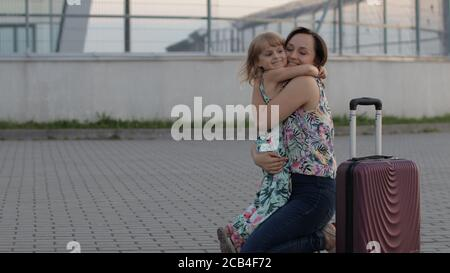 Woman meet her little daughter kid near airport terminal with open arms. Long-awaited meeting. Joyful mother and young child girl run to each other and embrace after long flight vacations, trip work