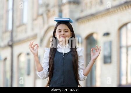 Calm the mind. Little child do meditation outdoors. Small girl do mudra hands holding book on head. Meditation for mental balance. Meditation course for beginner. School and education. Best therapy.