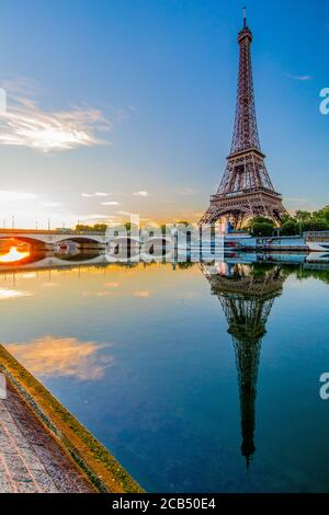 View of the Eiffel Tower at sunrise with a reflection in the River Seine; Paris, France.