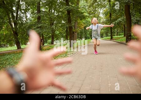 Beautiful smiling girl running to her mother in the park Stock Photo