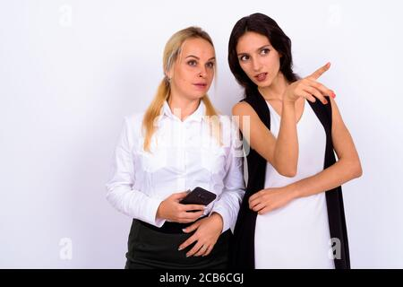 Portrait of two young beautiful businesswomen using phone together